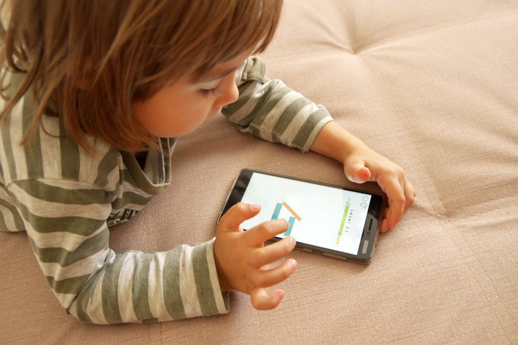 Cute kid girl play game on smart phone